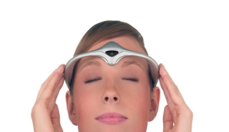 A woman wearing a Cefaly device