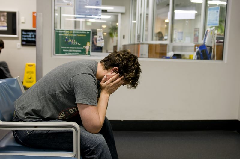 A distraught man with his head in his hands in a waiting room