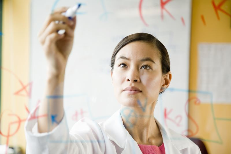 A doctor writing on a clear board.