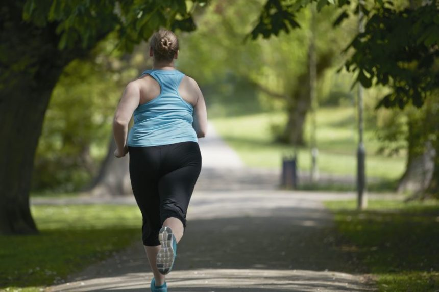 An overweight woman jogging