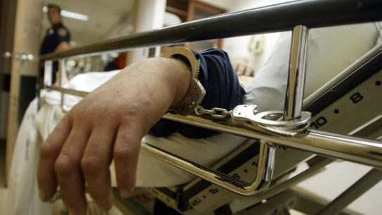 A patient is handcuffed to a hospital bed