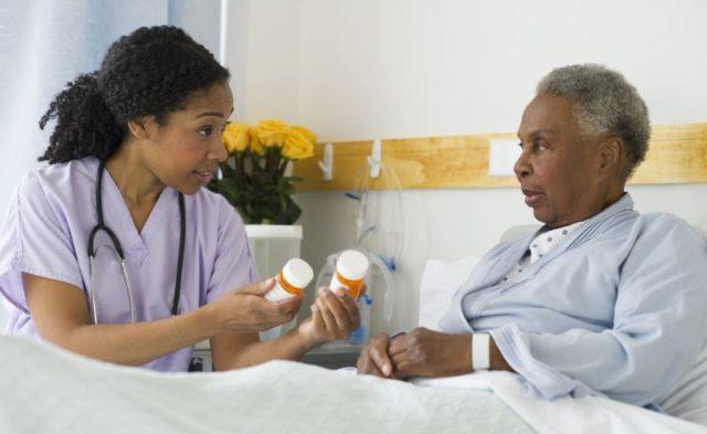 A nurse discussion prescriptions with patient post-surgery