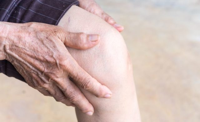 An elderly person holding their knee in pain