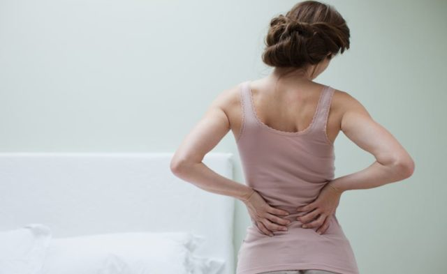 A woman holding her lower back in pain
