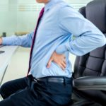 A man in an office chair with low back pain