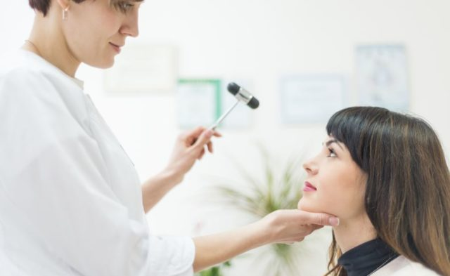 A physician examining a patient with migraine