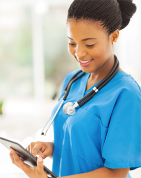 Healthcare professional working on a tablet.
