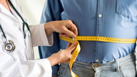 A doctor takes measurements of an overweight patient.