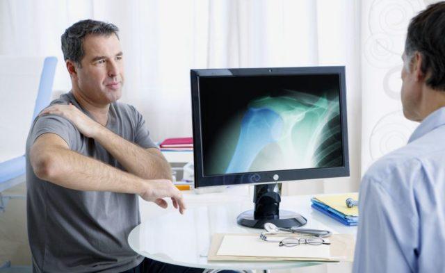 A man with shoulder pain at a rheumatology consultation