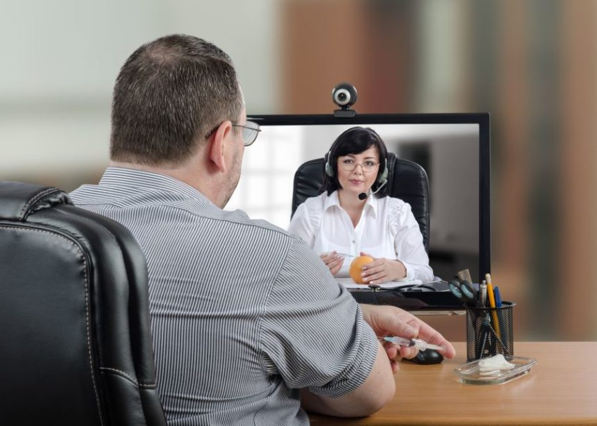 A patient speaking with a physician over a webcam
