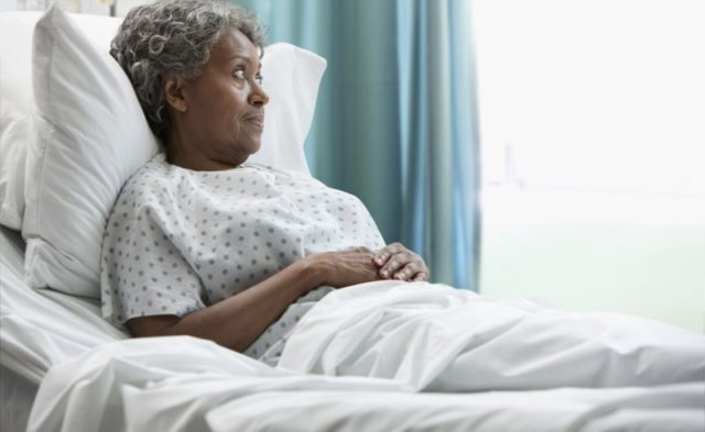 An elderly African American woman in a hospital bed