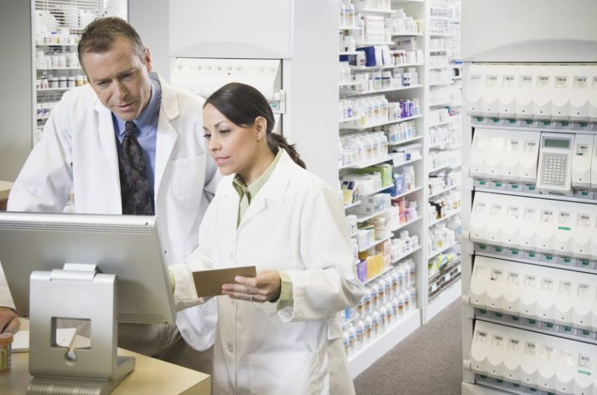 Two pharmacists looking over a computer in a pharmacy
