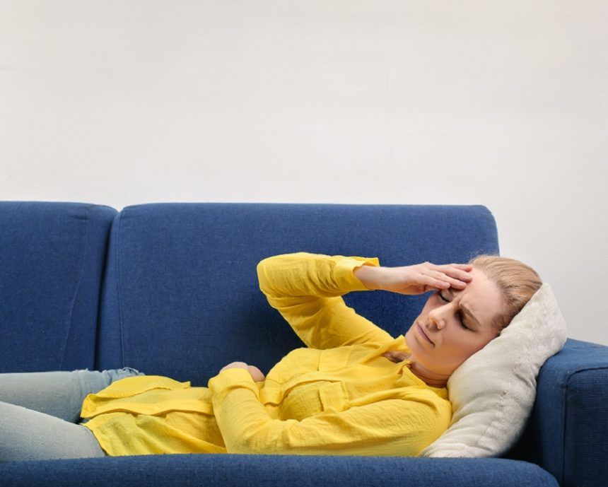 woman laying on a couch with her hand on her head