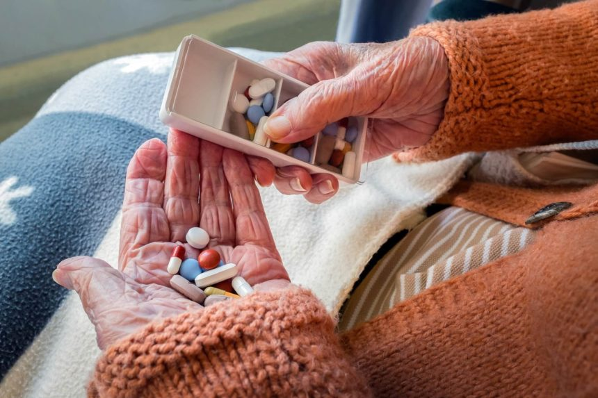pills in senior woman's hand