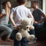 boy holding toy behind his back parents fight