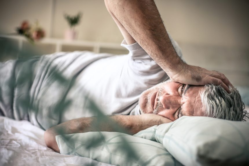 older man in bed with head pain, headache, migraine