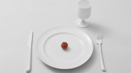 High Angle View Of white glass, fork, knife and plate with a cherry tomato on a table