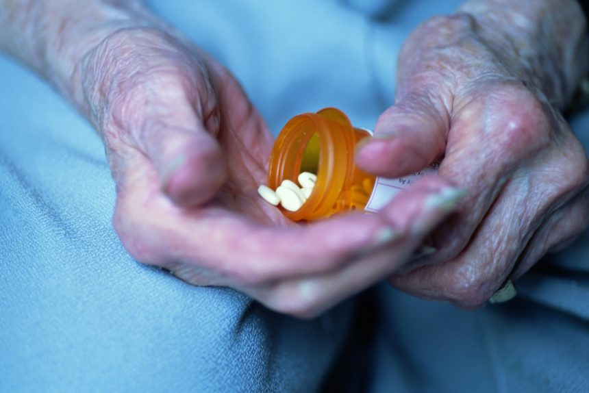 Elderly hands pouring medication out of bottle