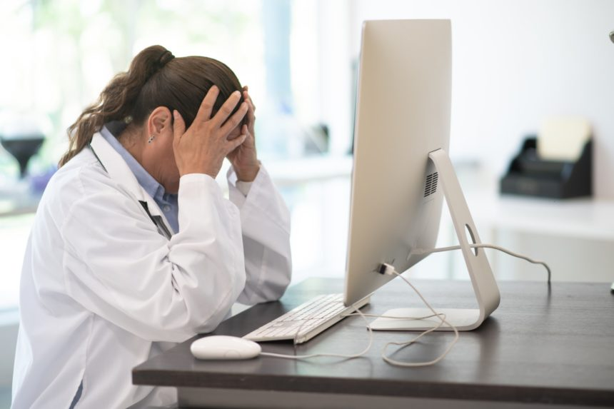 Female physician looks stressed in front of a computer.