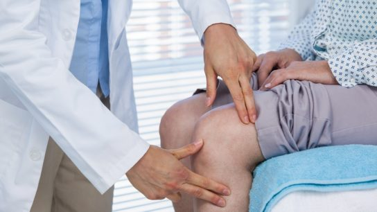 woman receiving knee exam, osteoarthritis