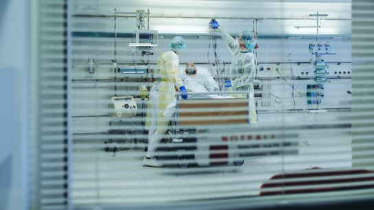 Doctors behind sunblind caring for patient in emergency care unit of a hospital with respiratory equipment